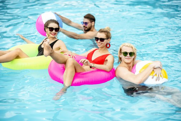 Group of a happy friends having fun, swimming with inflatable toys in the swimming pool outdoors during the summertime