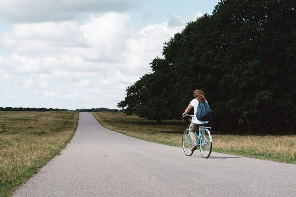 Smiling pretty young woman riding bike in a country road in the park