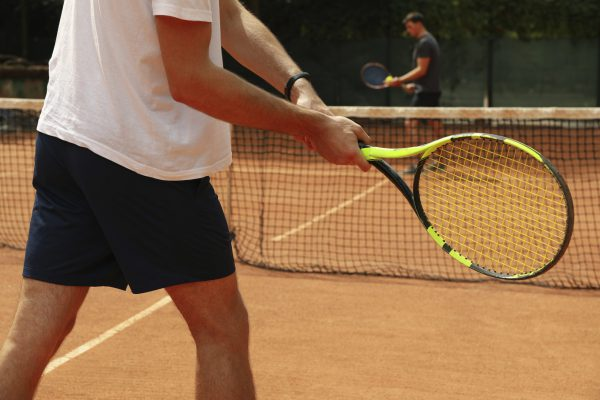 Two men playing tennis on clay court
